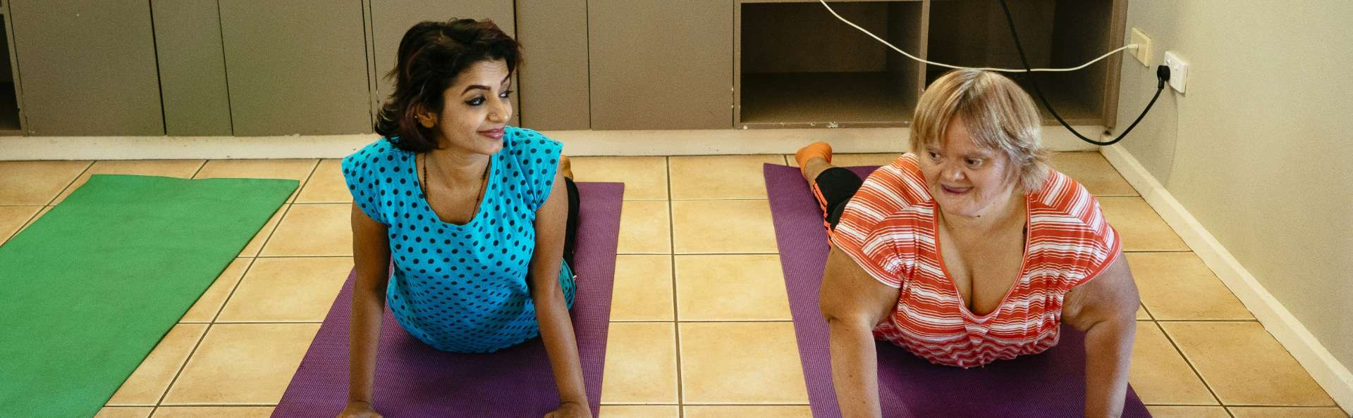 Teacher and participant stretch during a yoga class, as part of an Adult Day Service activity
