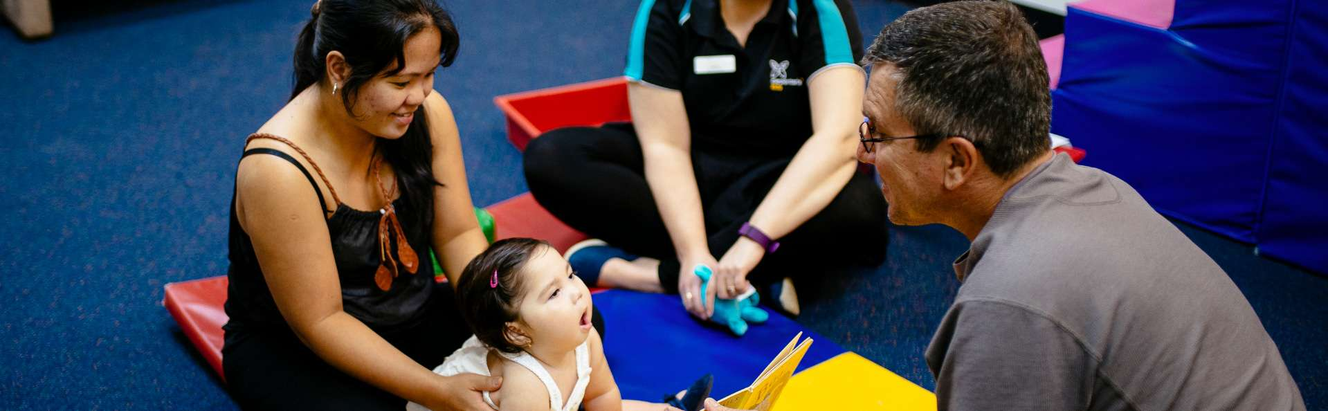 Child enjoys a story with her parents during a therapy session