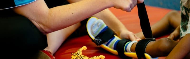 Therapist assists child with leg splints