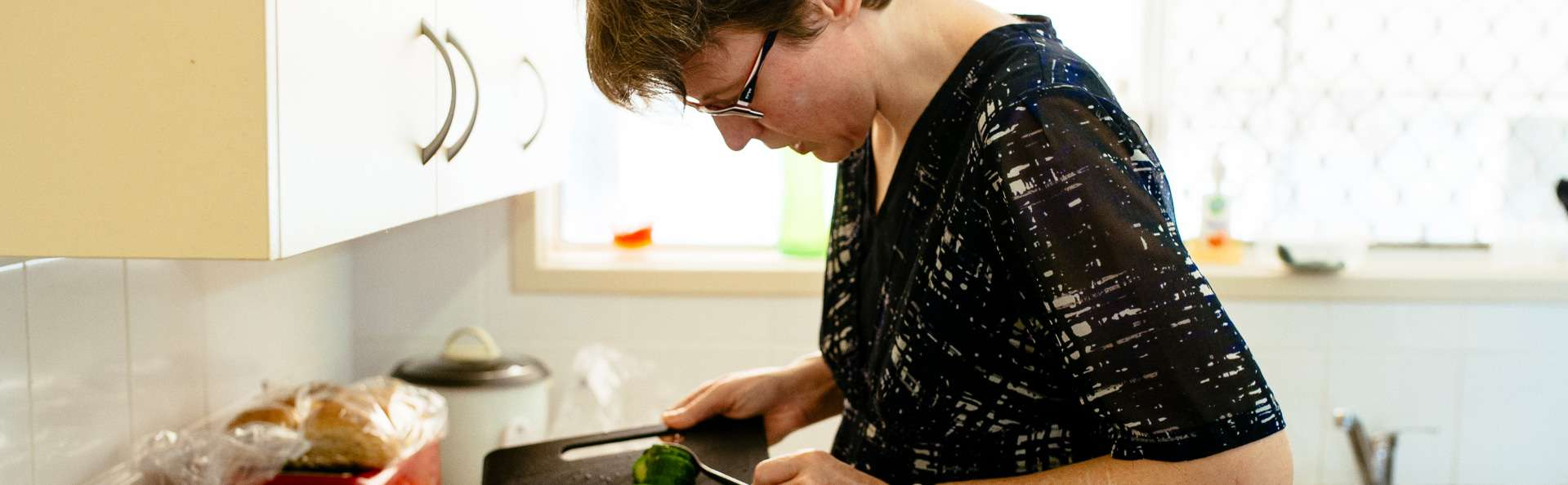 Supported Independent Living client prepares a salad for lunch