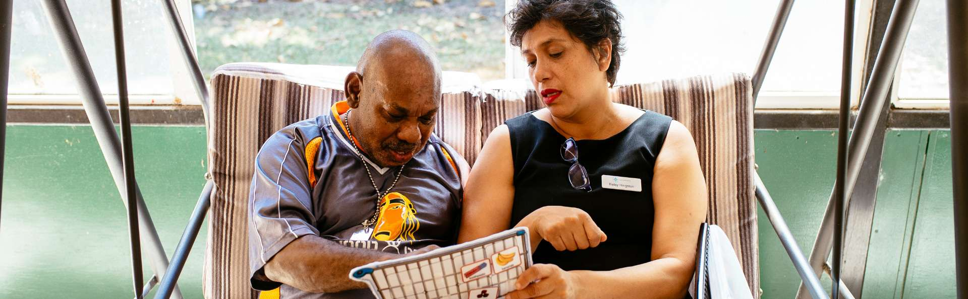 Allied Health worker assists a client to communicate with a visual tool