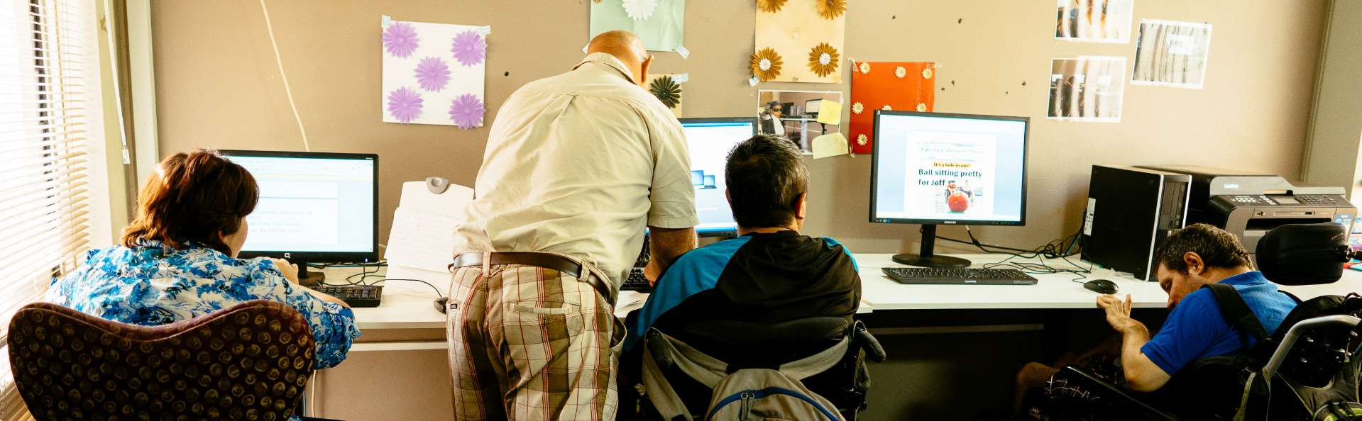 Three Adult Day Service participants enjoy time learning new computer skills, assisted by a Support Worker