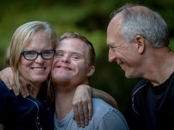 Mother embraces son with Down's Syndrome while father looks on