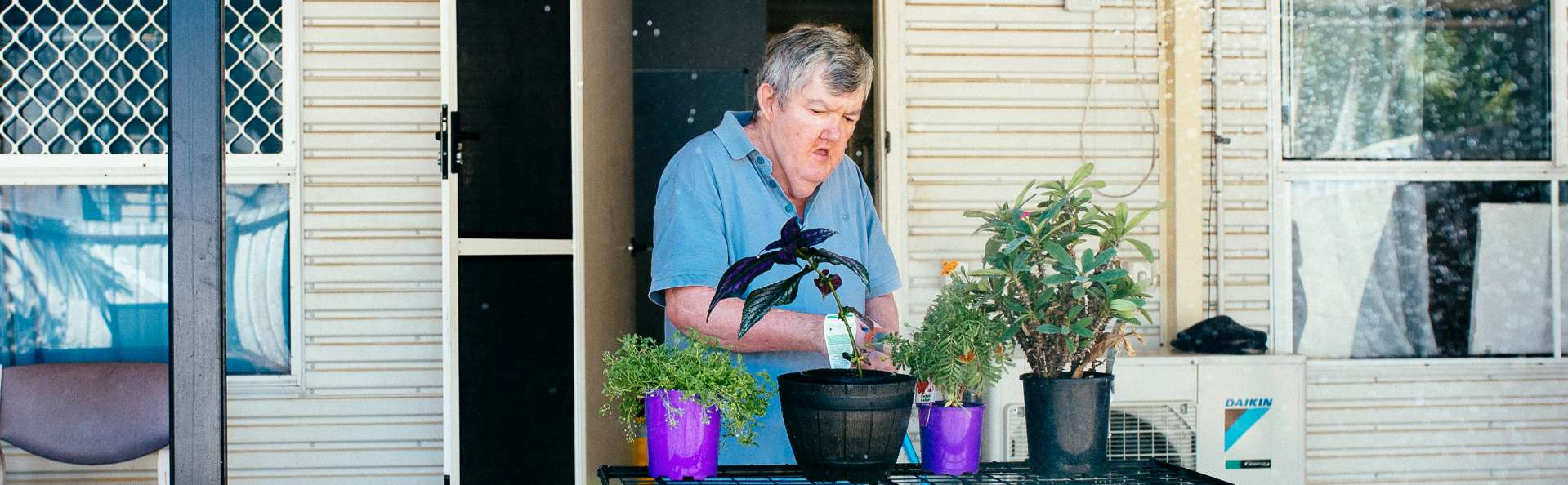 Supported Independent Living client enjoys tending to his plants